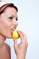 young woman licks at a citron