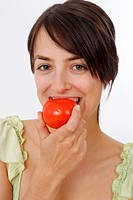 young woman eats tomato