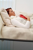 young woman with book, sleeping on a couch