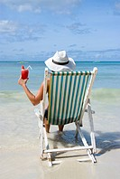 woman with cocktail sits in a folding chair at the beach, enjoying holidays, Philippines