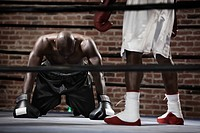 African boxer kneeling on boxing ring mat