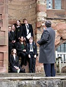 teacher taking a picture of a group of pupils in the ruins of the Cathedral of Coventry, United Kingdom, England, Coventry