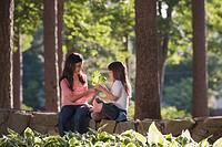 Hispanic sisters holding leaf