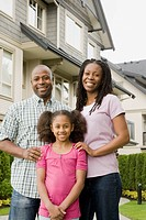 African American family standing outside house