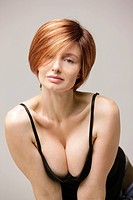 A woman with a Victoria-Beckham-haircut and a black top, showing her cleavage