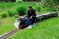 Pensioner sitting on a model railway in a public park, Waldkraiburg, Upper Bavaria, Germany, Europe