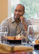 African man sitting at set table