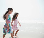 Hispanic sisters walking on beach