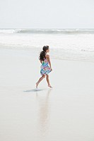 Hispanic girl walking on beach