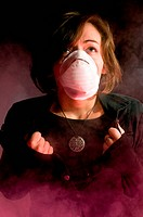 Woman in medical mask inside clouds of smoke