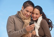 Hispanic couple looking at cell phone