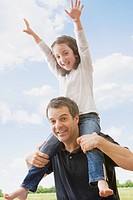 Hispanic father carrying daughter on shoulders