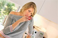 young blond woman in a pyjamas, drinking a coffee in the kitchen, Germany