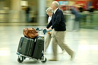 elder couple with their luggage on a trolley at the airport