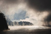 Austria, Salzkammergut, Lake Wolfgangsee with fog and clouds