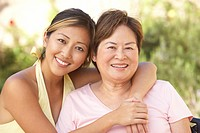 Senior Woman With Adult Daughter In Garden Together