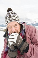 Italy, South Tyrol, Seiseralm, Man outdoors shivering from cold, portrait, close_up