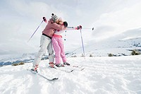 Italy, South Tyrol, Seiseralm, Young couple on skis in snow field, kissing