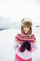Italy, South Tyrol, Seiseralm, Woman standing in snow field, smiling, portrait