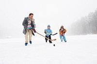 Italy, South Tyrol, Seiseralm, Father and children 4_5 playing ice hockey