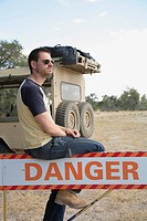 Africa, Botswana, Okavango Delta, Man sitting on danger sign