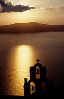 Church dome and bells silhoueted in the sunset at Thira, Santorini, Cyclades, Greece