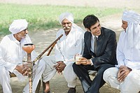 Businessman discussing with three farmers