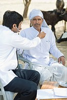 Doctor examining a farmer with a stethoscope