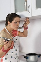 Woman tasting soup in the kitchen
