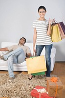 Woman holding shopping bags with a man sitting behind her