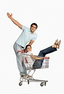 Man pushing a woman sitting in shopping cart