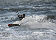 Kitesurfer showing off his board while carving on the North Sea in Zeeland, The Netherlands