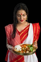 Beautiful woman in a Bengali sari holding pooja thali