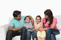 Close_up of a family sitting on a couch and smiling