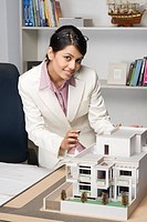 Portrait of a businesswoman near a model home in an office