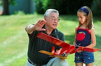 grandfather explaining a model aircraft to his granddaughter