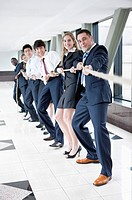 Business people standing in a row and playing tug_of war