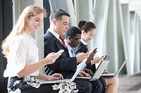 Business people sitting in a row with laptop, each using mobile phones