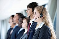 Business people wearing headsets in a row and smiling