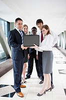 Business people standing and looking at the laptop together