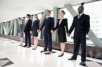 Business people standing in a row and holding hands together