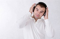 Young man listening music with headset and looking down with smile