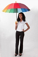 Young woman standing with arms akimbo and holding an umbrella