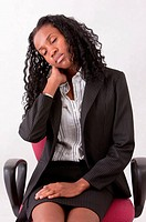 Businesswoman resting on chair with eyes closed and head in hand