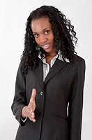 Young businesswoman reaching one hand and smiling at the camera