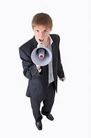 Young businessman shouting with megaphone and looking up