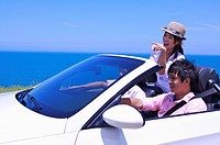 Three people driving in the car and enjoying leisure activity together
