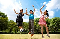 Three children jumping in mid_air with arms outstretched and smiling