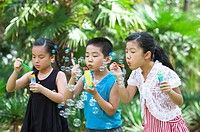 Three children standing in a row and blowing bubbles together