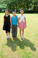 Three children standing in a row and holding hands together